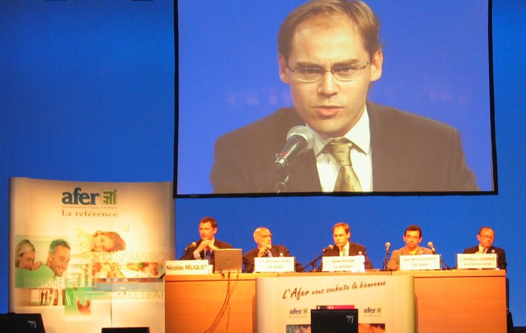 En animant des conférences de l'Afer (ici à Lyon en 2004), Gilles Pouzin (à l'écran) rédacteur en chef du Revenu, apprend par la rumeur que son employeur est courtier d'assurance vie Afer, comme la presse le révèle en 2011.